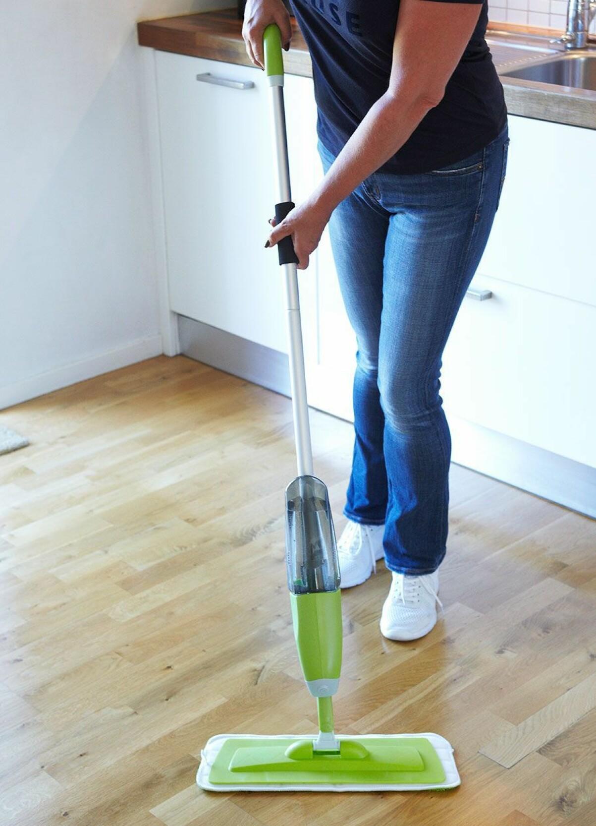 Kvinna våttorkar golv med en spraymopp.