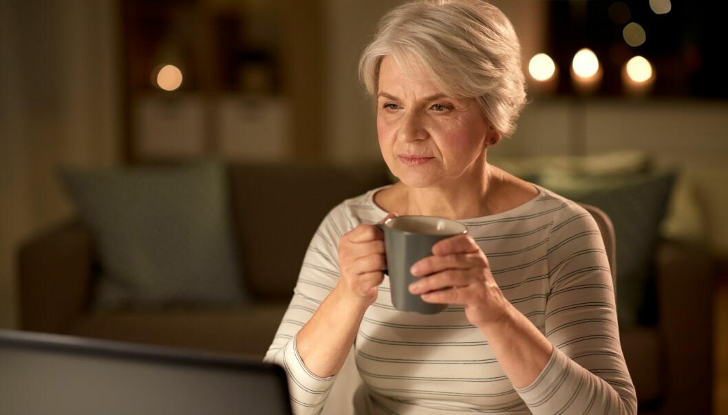 Kvinna sitter vid datorn och dricker kaffe.