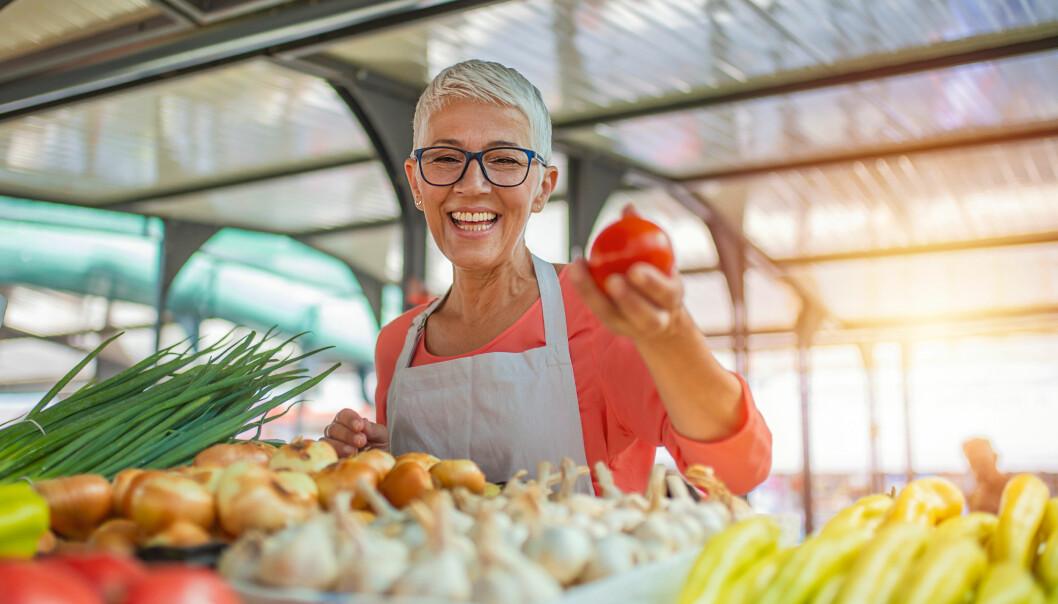 Kvinna bland grönsaker.