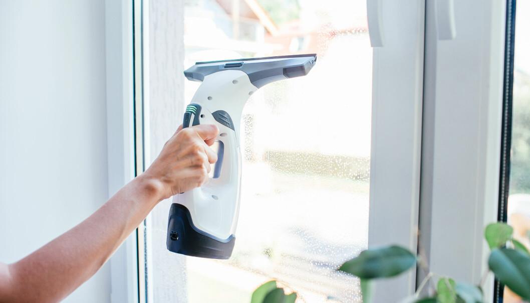 Kvinna putsar fönster med en fönstertvätt