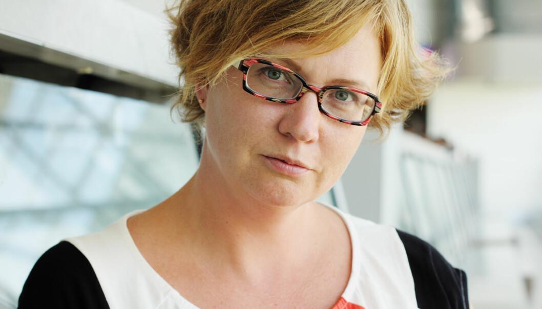 Kvinna i 30-40-årsåldern, med halvkort hår och glasögon, tittar allvarligt in i kameran.