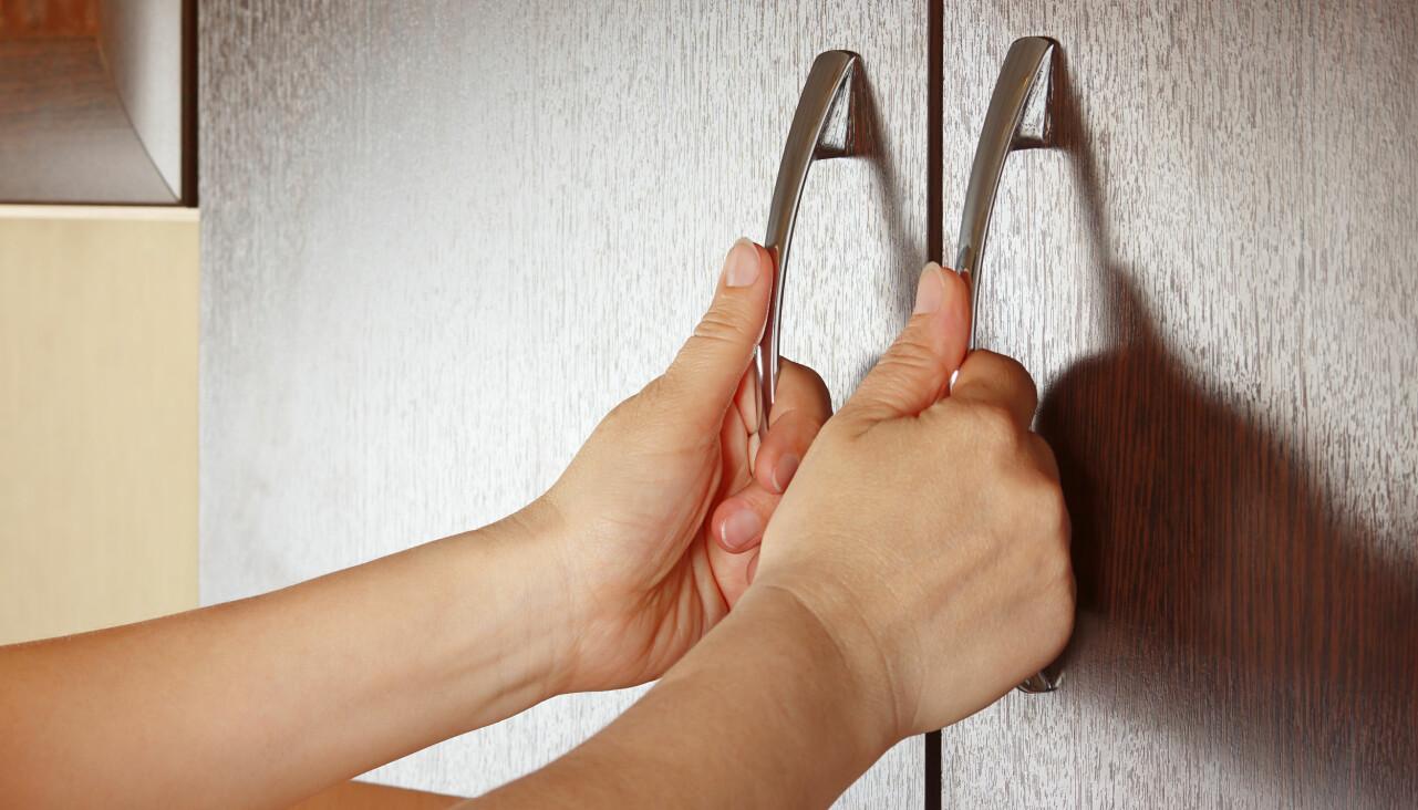 Kvinnohänder öppnar köksluckor.
