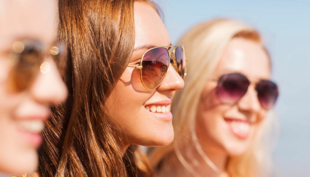 Tre kvinnor där en är i fokus. De är utomhus i solen och bär solglasögon.