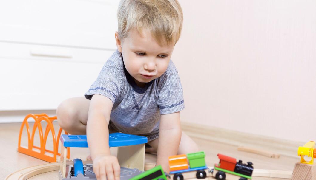 Liten pojke sitter och leker med tågbana på ett golv