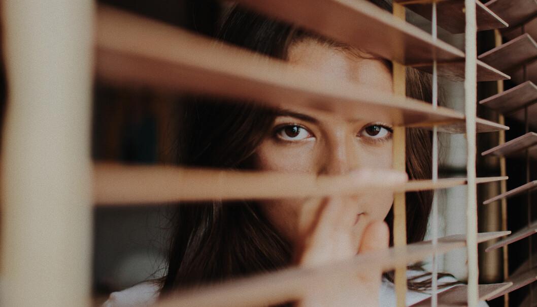 Deprimerad kvinna tittar fram bakom en gardin
