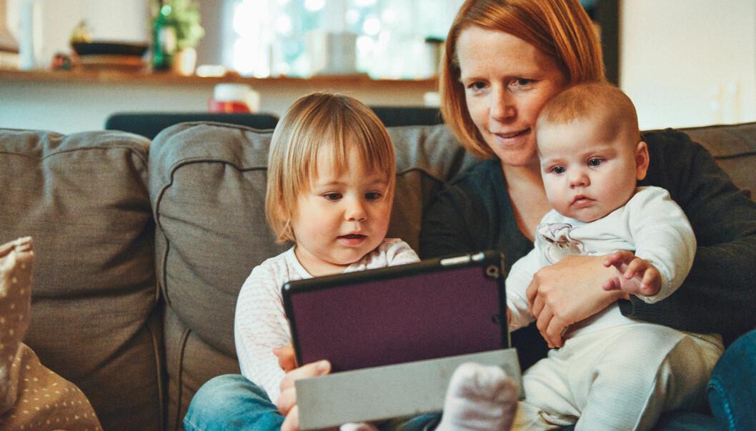 Mamma sitter i en soffa med två barn och en läsplatta