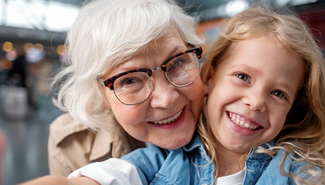 Mormor och barnbarn kramas och ser glada ut