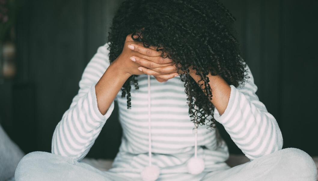 Kvinna sitter med huvudet i händerna och ser ledsen och osäker ut