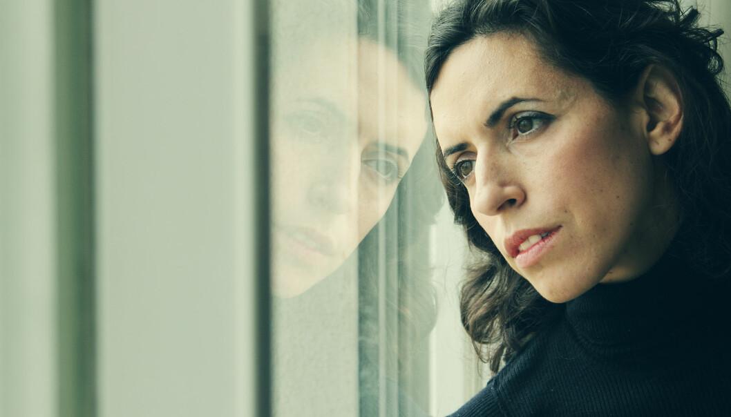 Ledsen kvinna tittar ut genom ett fönster