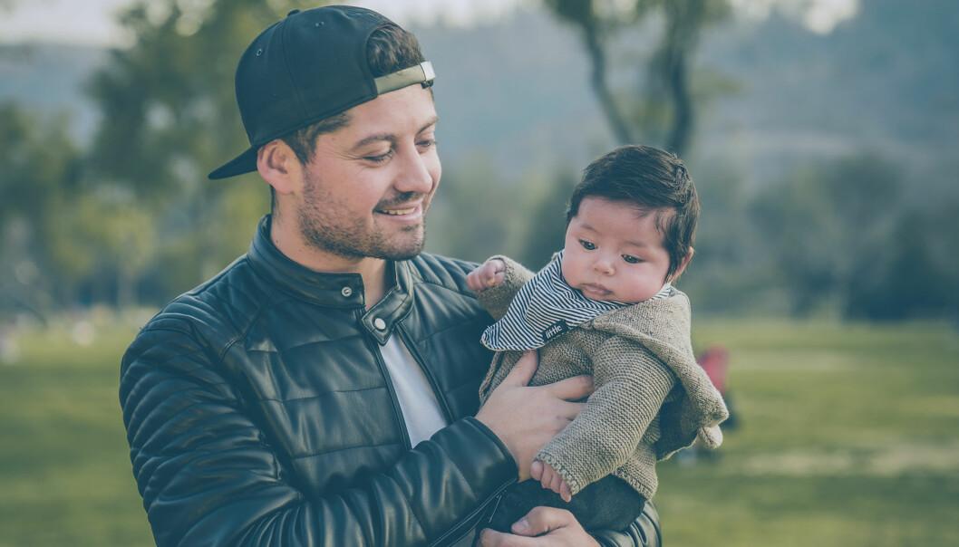 Ung pappa håller sin bebis i famnen