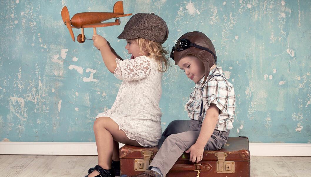 Två barn sitter på en resväska och leker