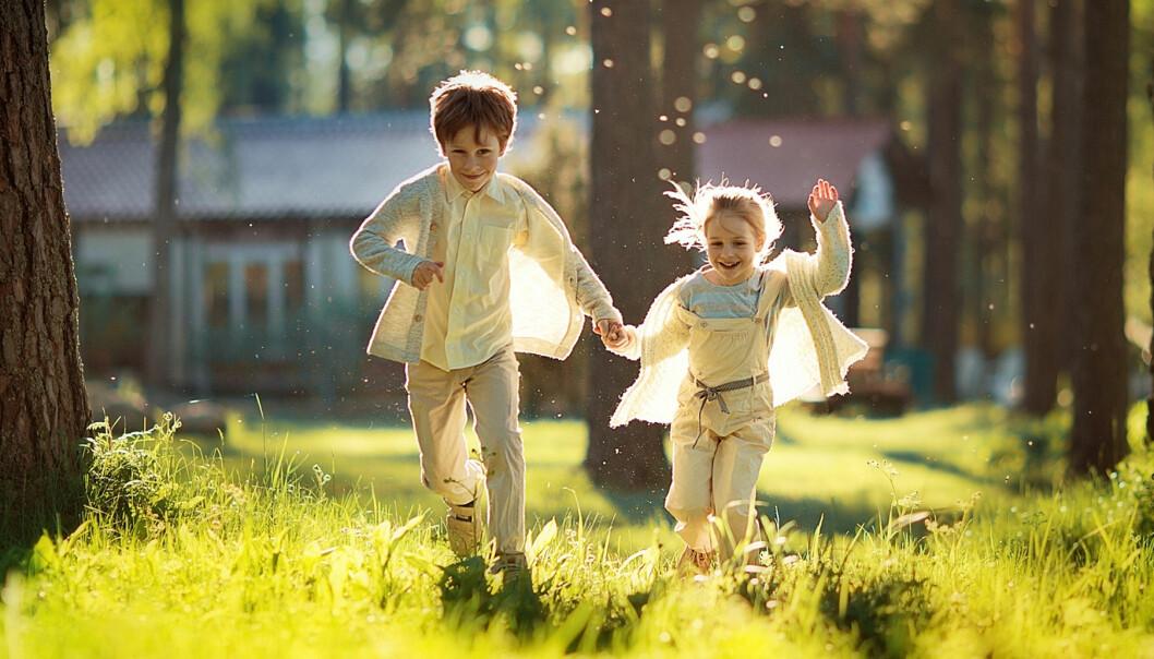 Två barn springer och leker i en lummig trädgård
