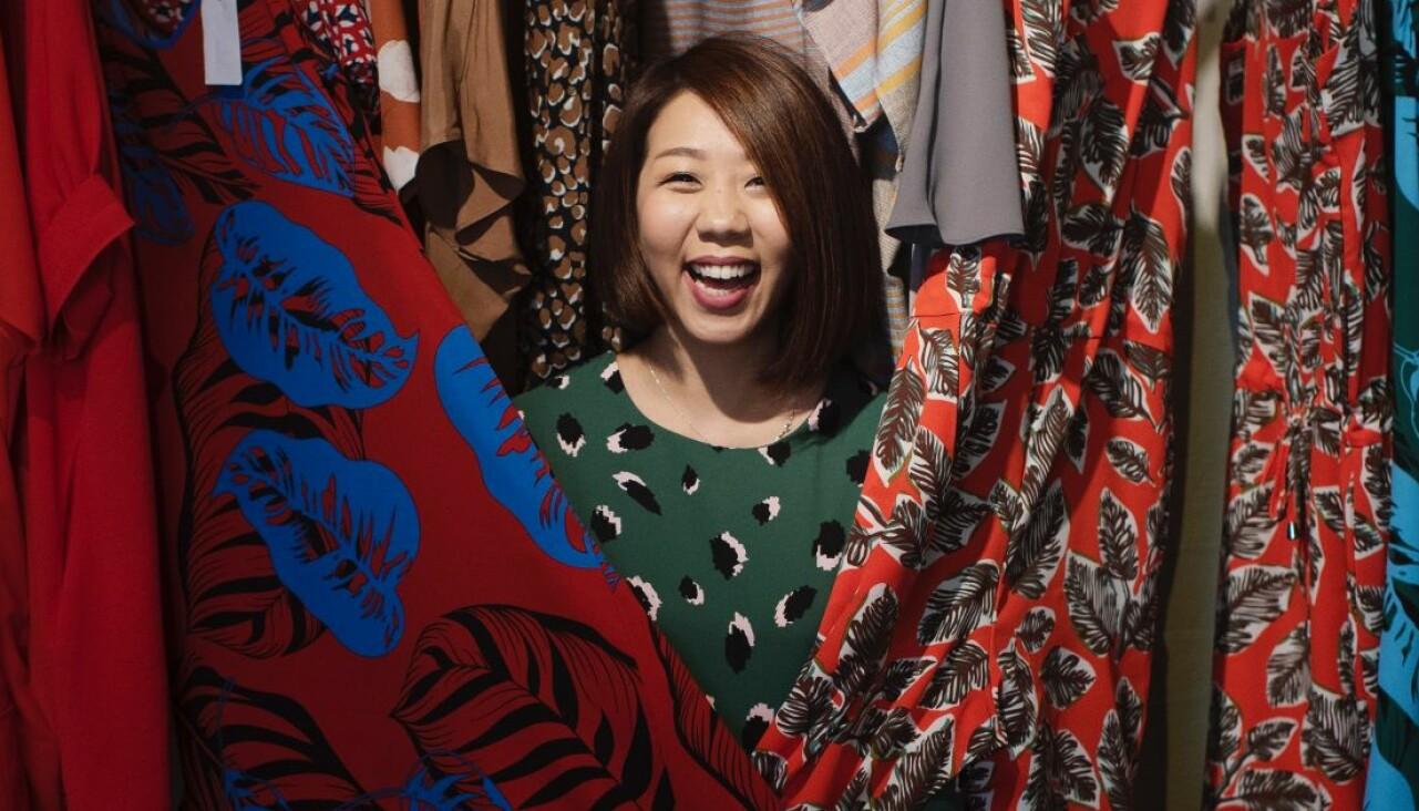 Leende kvinna känner på kläder som hon skulle kunna hyra.