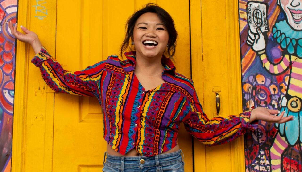 Leende kvinna poserar framför en gul dörr.