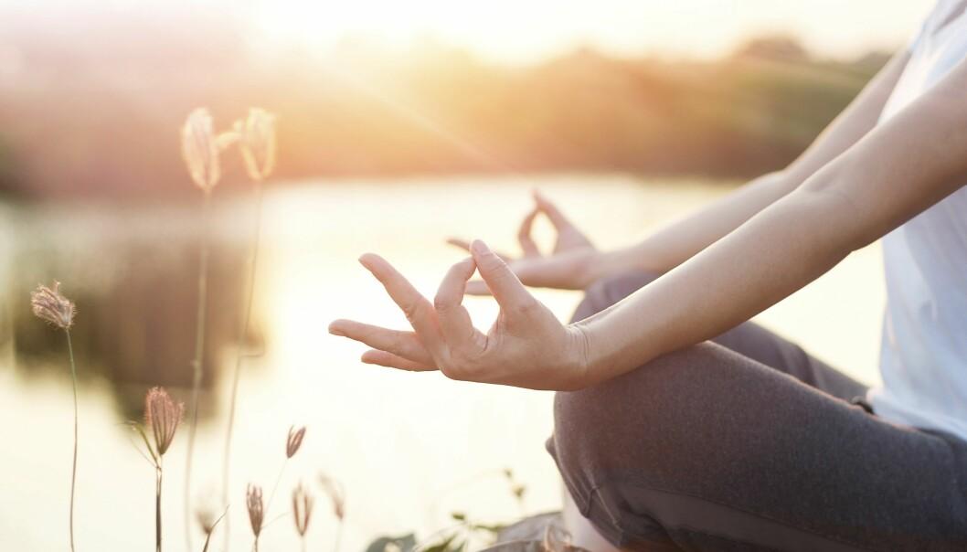 Kvinna gör yoga vid sjö, kanske för att lindra ibs.