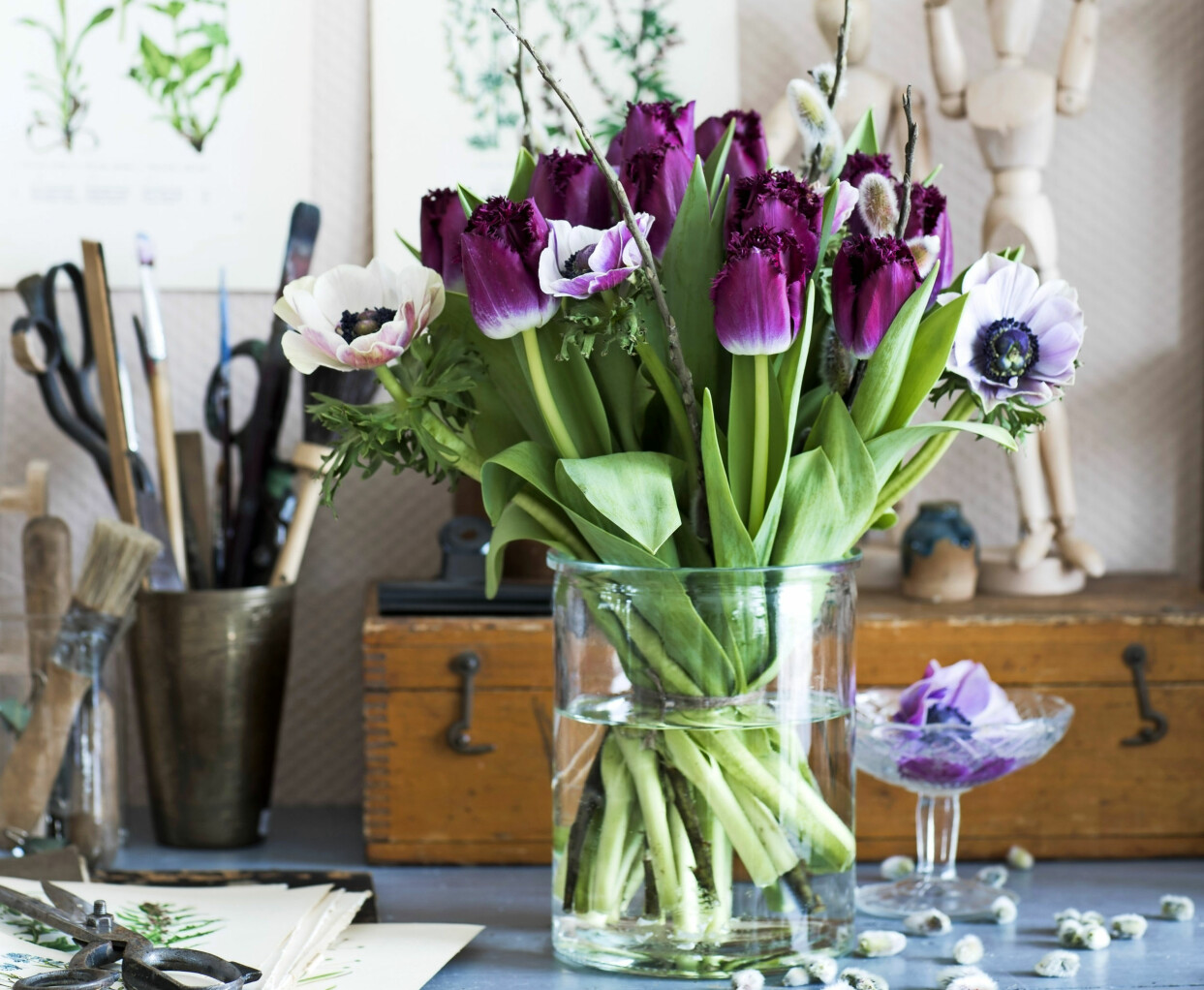 Lila bukett med tulpaner, anemoner och videkvistar.