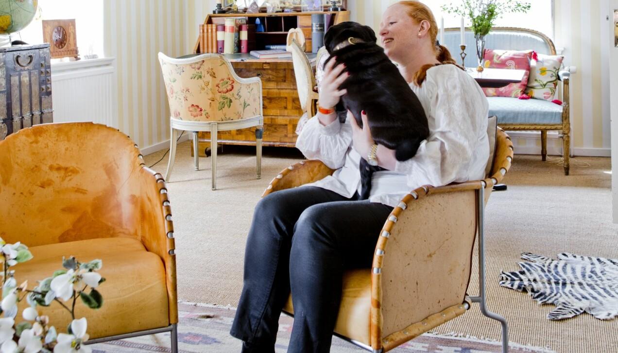 Maria Granström sitter i fåtölj med svart hund i knäet. Runtomkring syns äldre möbler och en rölakansmatta på golvet.