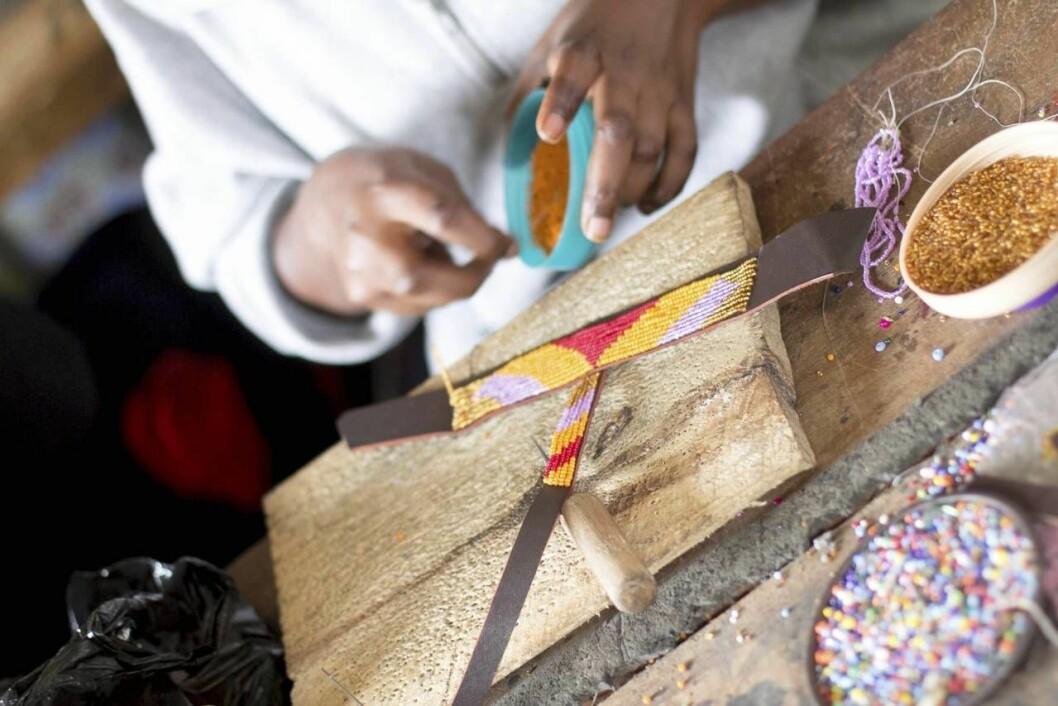Kvinna gör sandaler av pärlor