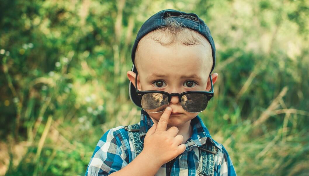 Liten pojke håller ner ett par glasögon och tittar in i kameran.