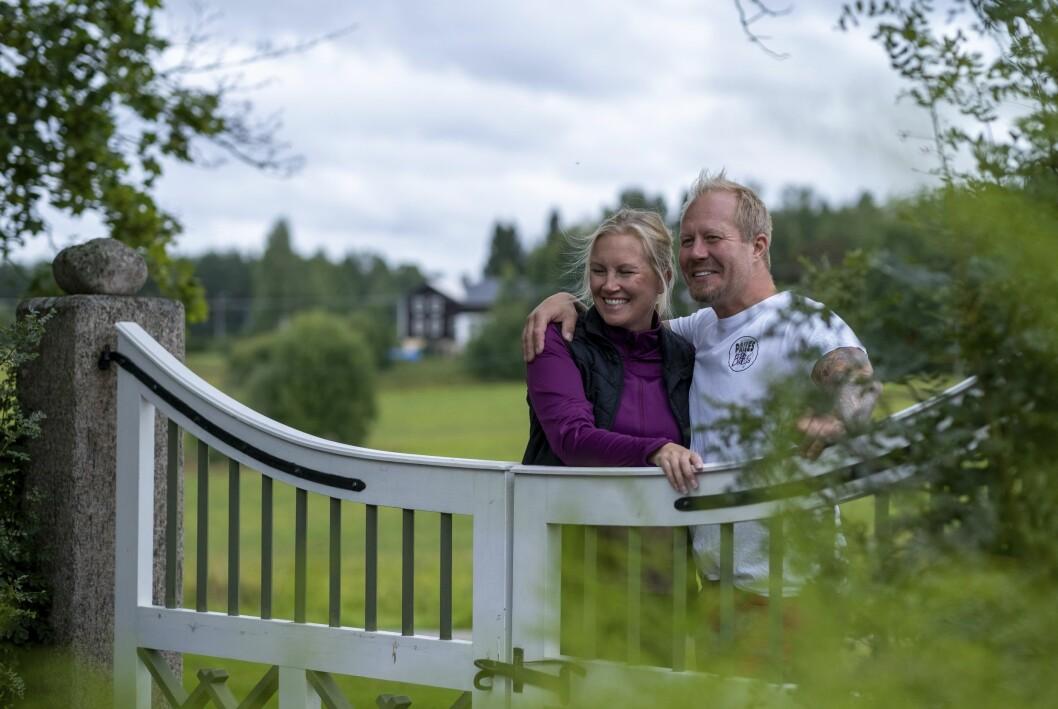 """Karin Ås och Jon-Erik """"Jeja"""" Andersson står och håller om varandra, lutade mot en grind i natursköna omgivningar."""