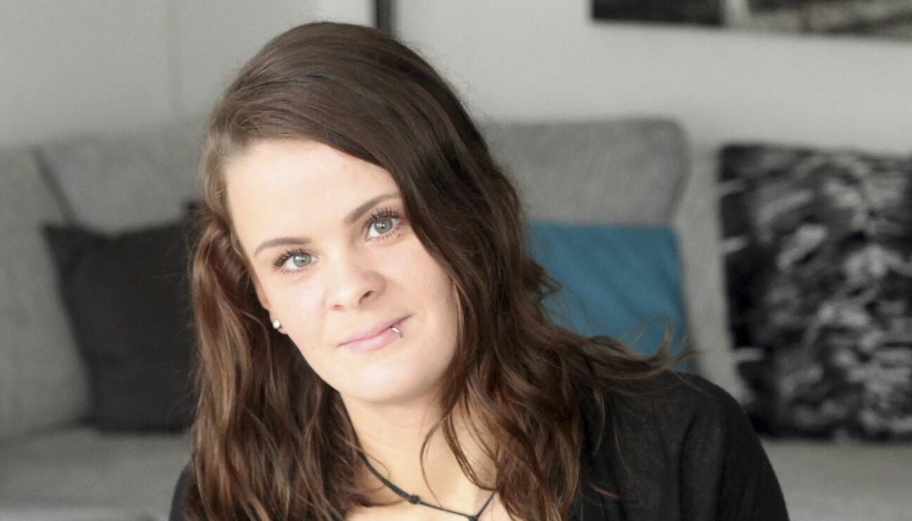 En ung kvinna med piercing i läppen ler lätt och tittar in i kameran.