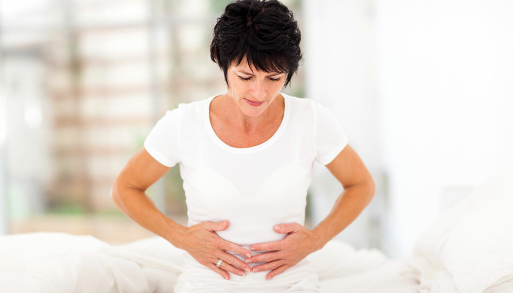 Vitklädd, mörkhårig, kortklippt medelålders kvinna håller sig för magen.