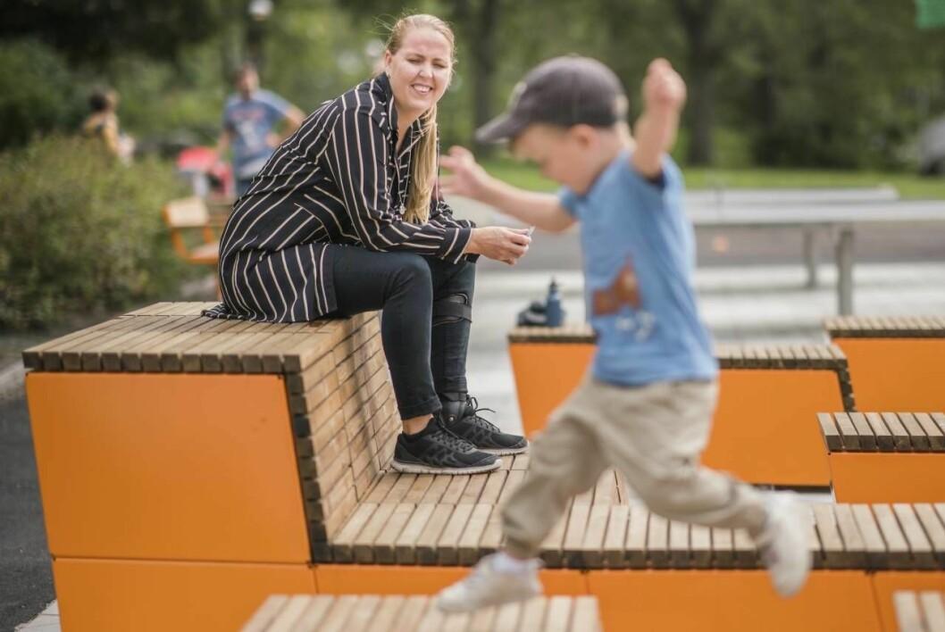 Maja, som ficks trike under graviditeten, sitter på lekplatsen och tittar när sonen leker.