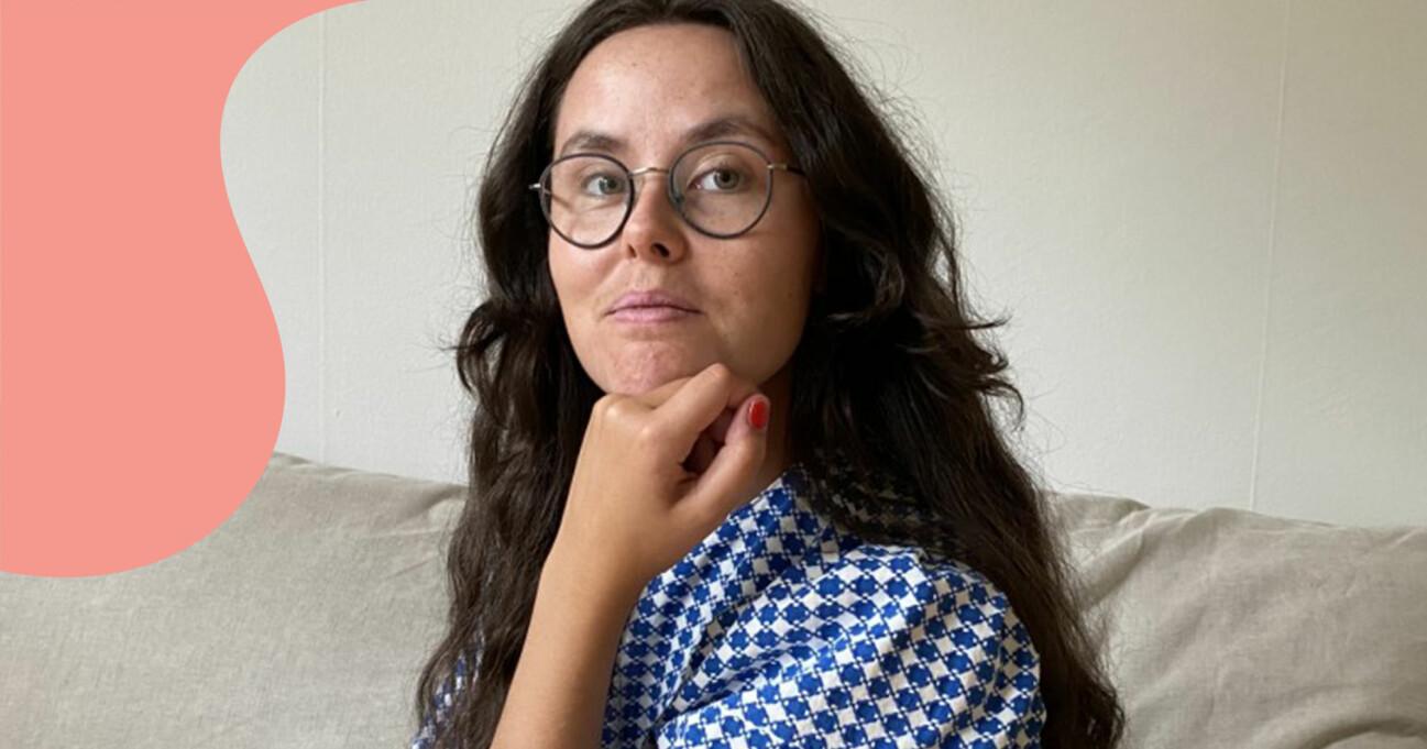 Maja Delborn har på sig en blå-vit klänning som hon sytt själv och tittar in i kameran. Hon sitter på en naturfärgad soffa som hon själv sytt överdraget till.