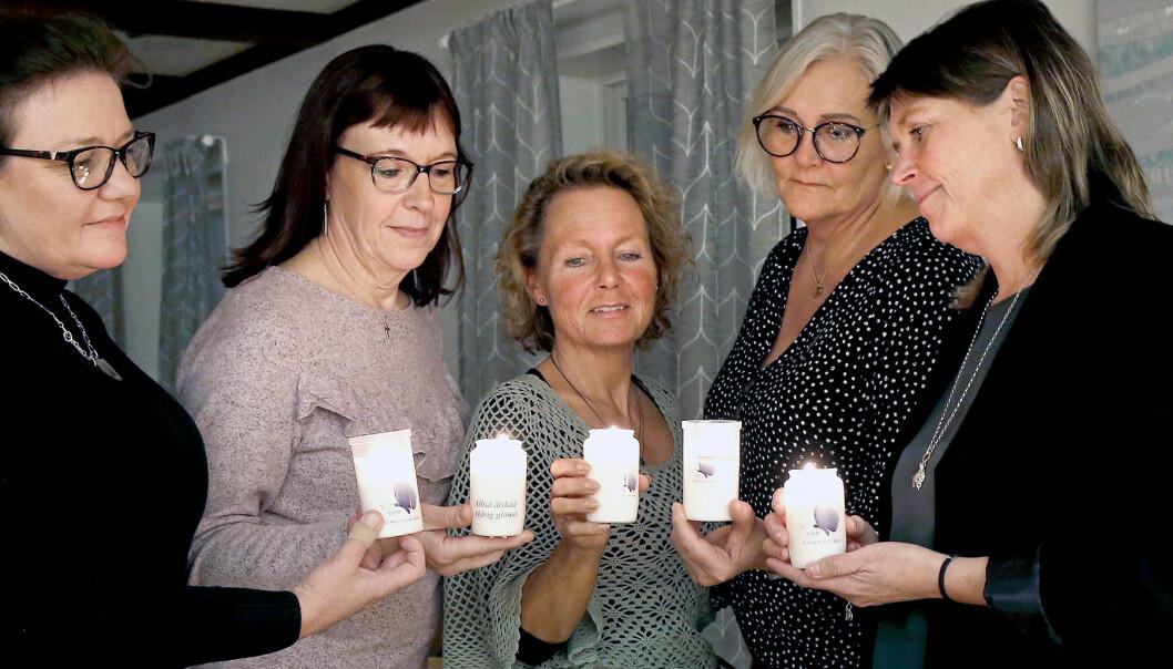 Fem mammor som alla förlorat sina söner står tillsammans med tända ljus