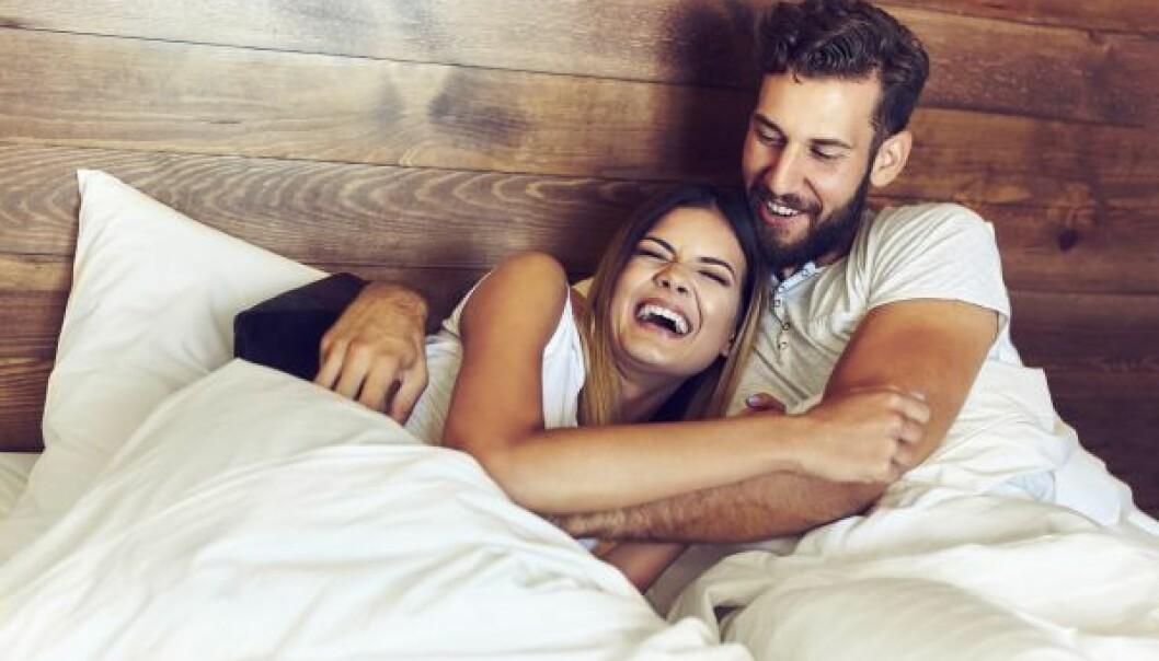 Man och kvinna skrattar och kramas i säng.