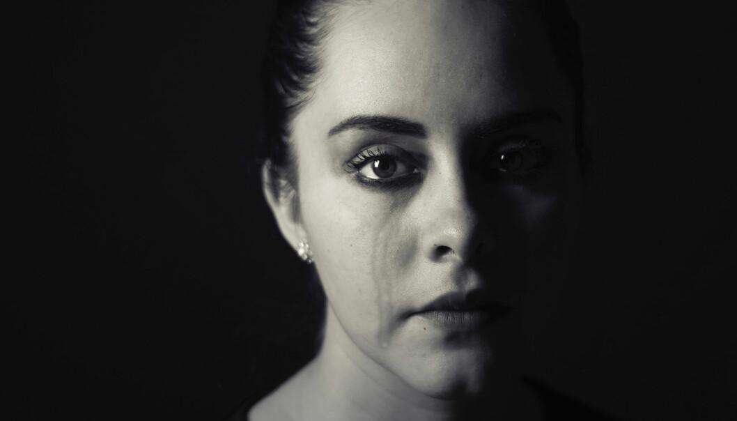 Kvinna gråter och tittar in i kameran