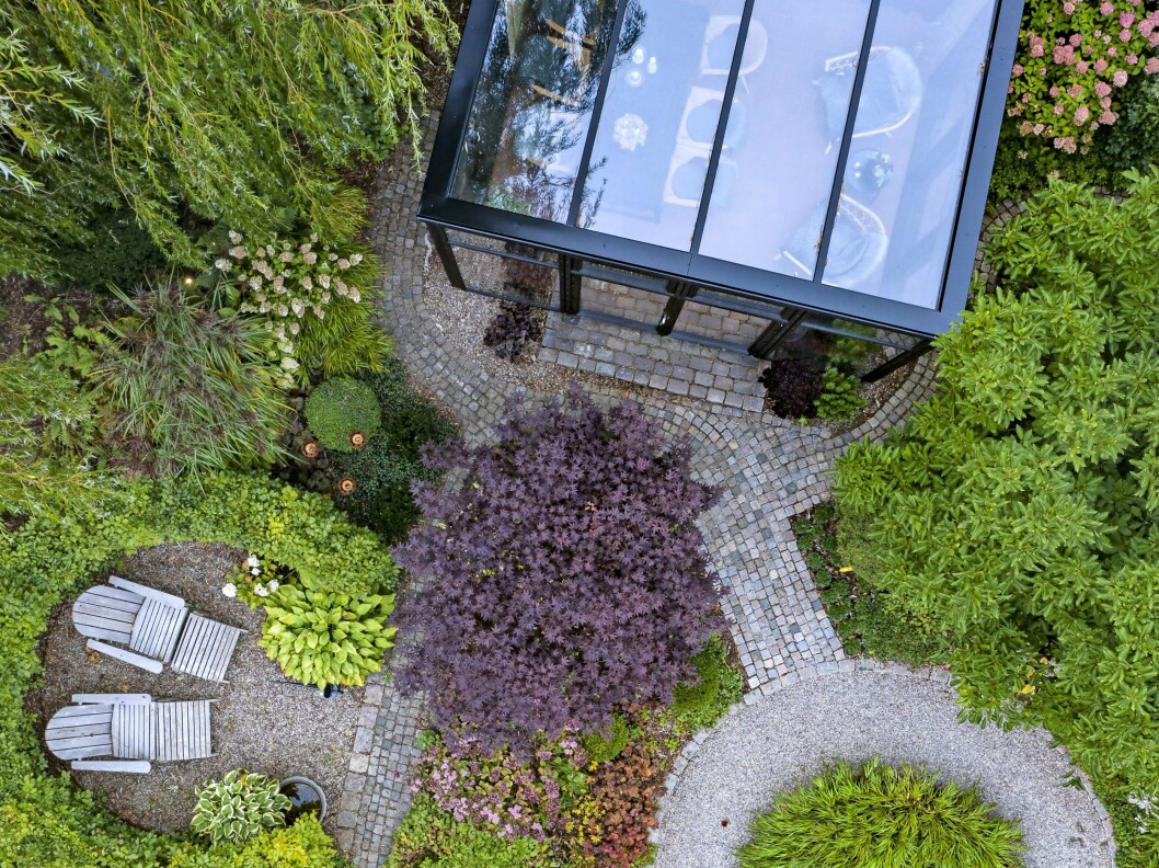 Trädgården är inte stor, men välplanerad. Det nya glashuset har fått överta studsmattans plats sedan barnen vuxit upp. Den stora pilen till vänster ger välbehövlig skugga på soliga sommardagar.