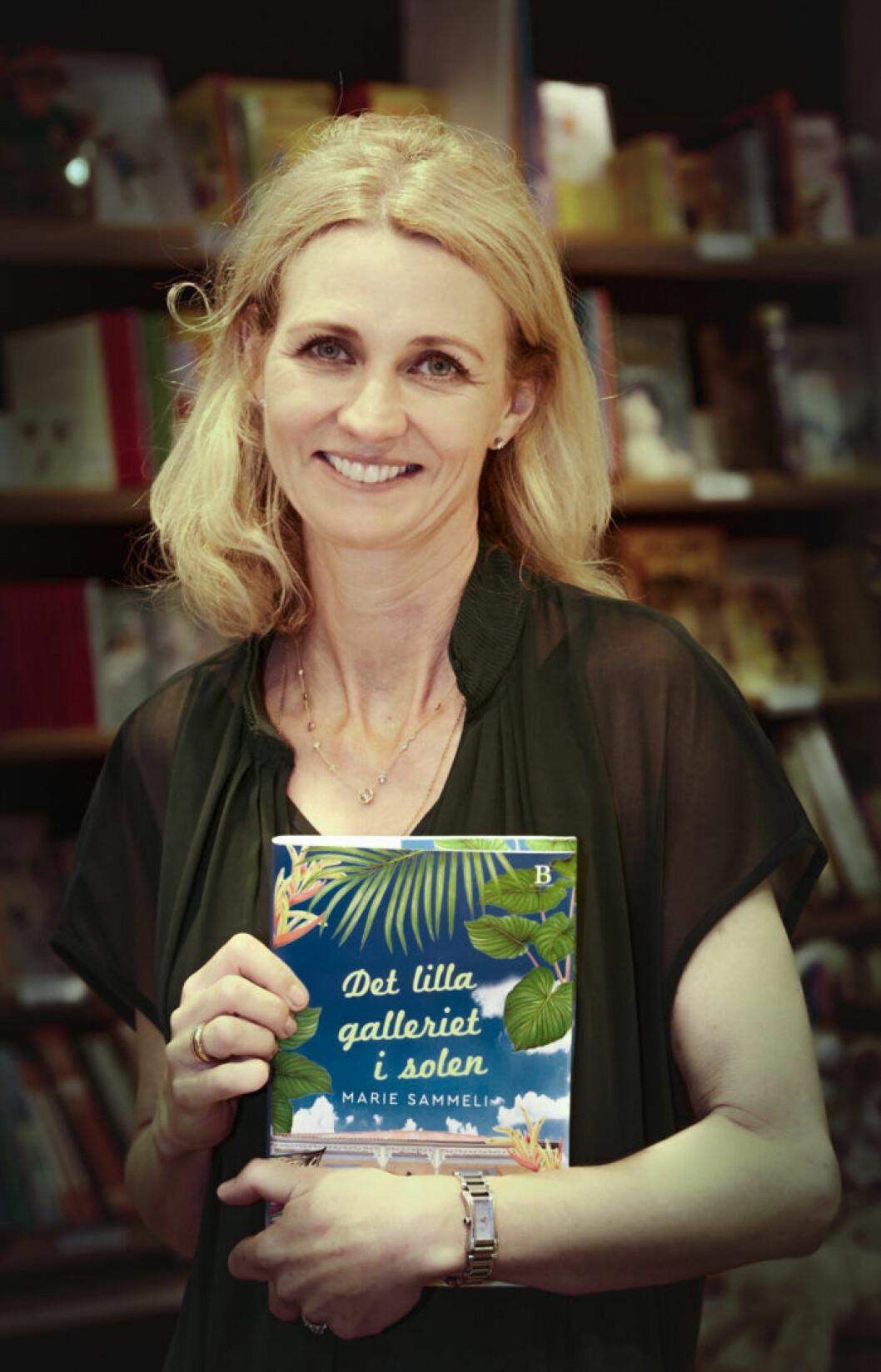 Marie Sammeli står i en bokhandel med sin egen bok Det lilla galleriet i solen i famnen.