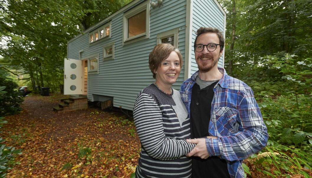 Marita och John står framför sitt tiny house på 16 kvadratmeter som ligger i en skogsdunge.