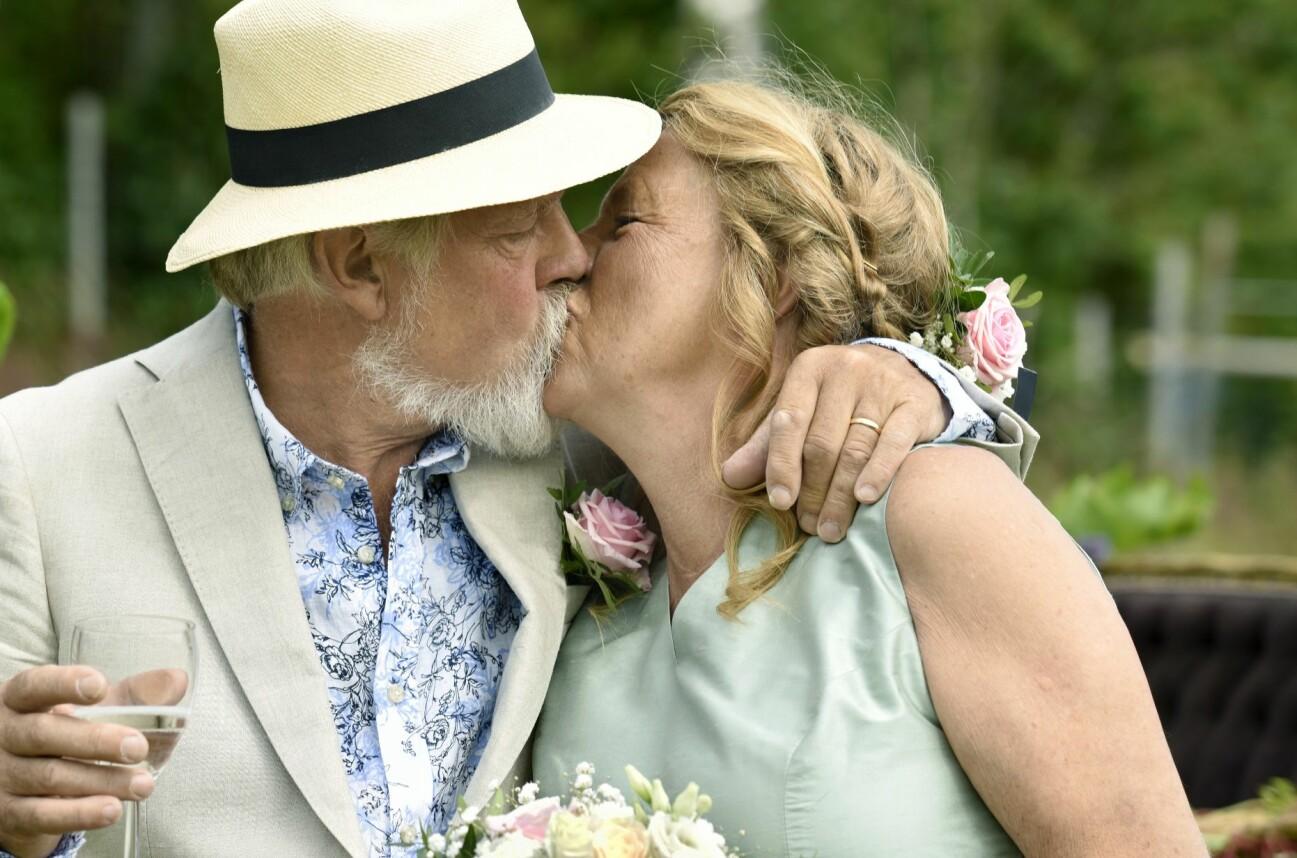 Brudparet pussar varandra, han i halmhatt hon med brudbukett.