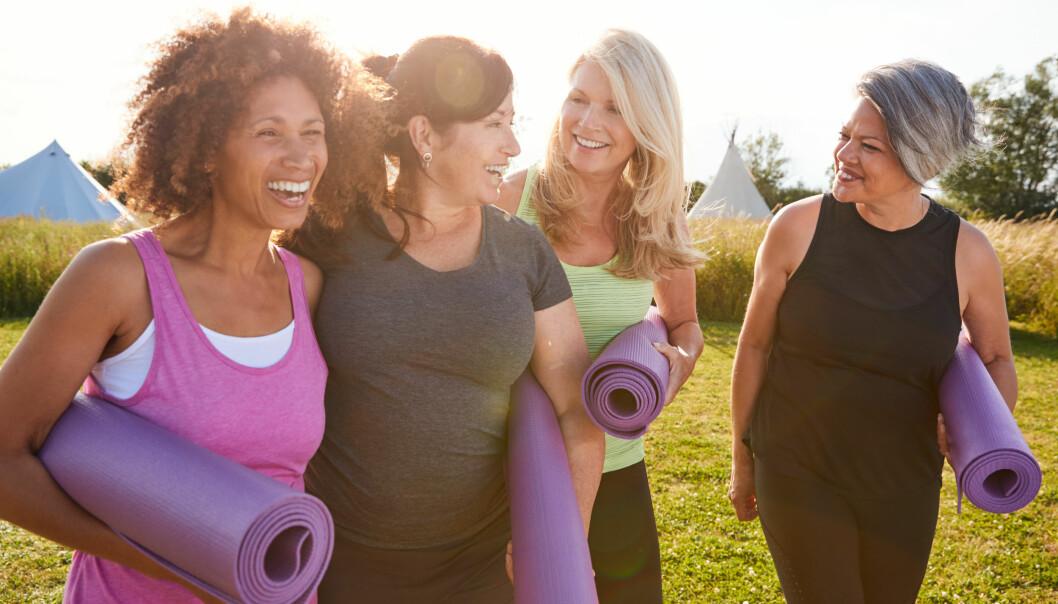 Kvinnor i medelåldern skrattar tillsammans ute i naturen och bär på yogamattor.