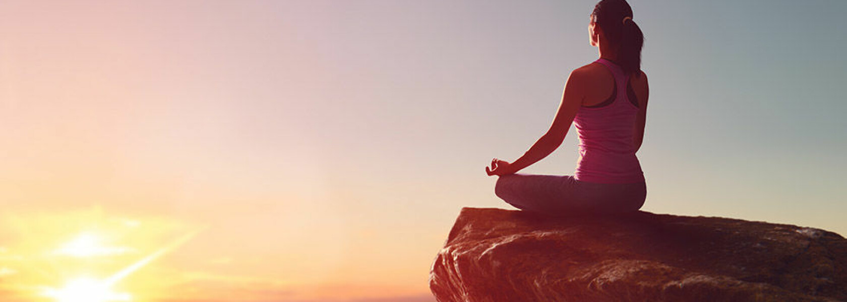 Woman practices yoga and meditates on the mountain.; Shutterstock ID 688367407