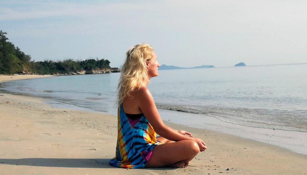 Anette sitter på en strand och utövar migränyoga.