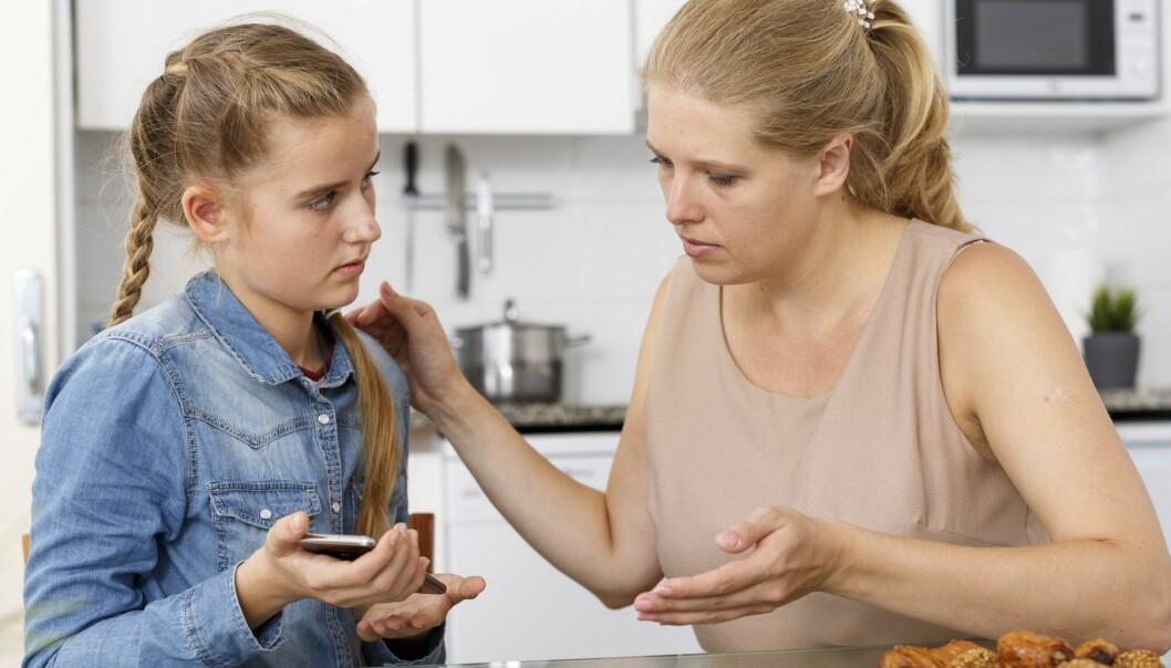Mor och dotter tittar på mobilen.