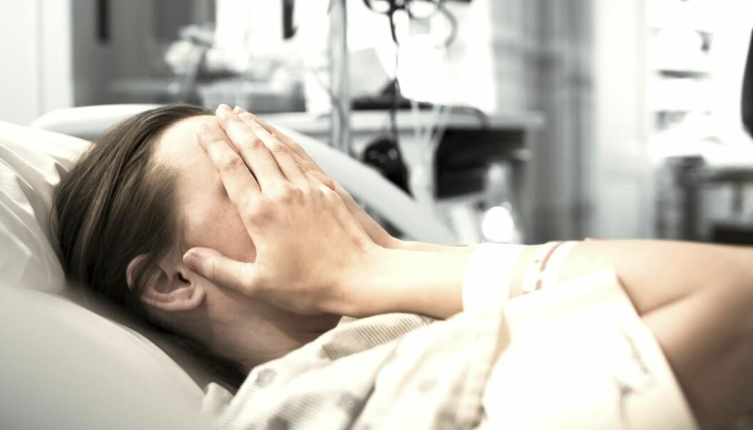 Ung kvinna ligger med händerna för ansiktet i en sjukhussäng