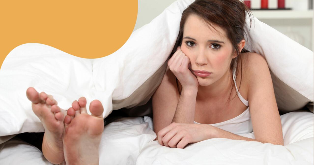 Missnöjd kvinna under täcke i sängen.
