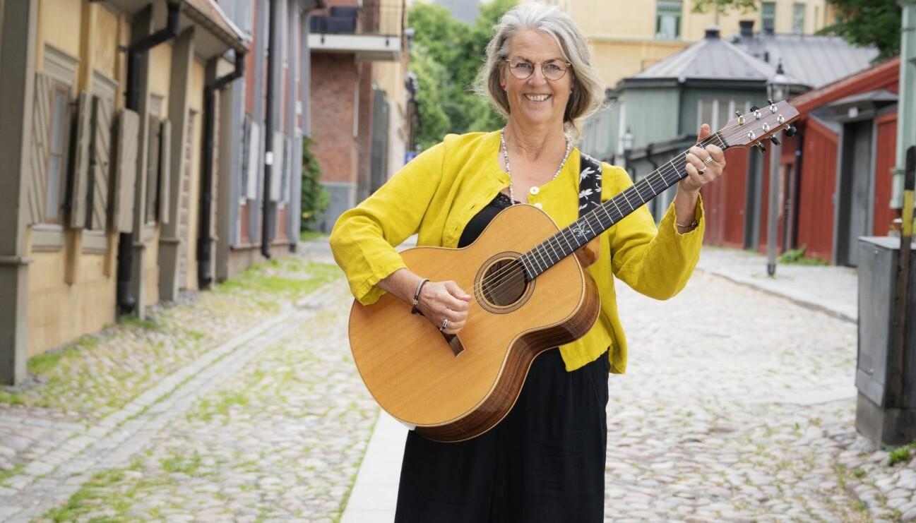 Mona Johansson står på gatan, tar ett ackord på sin gitarr och berättar om hur hon gick i pension vid 61-års ålder för att satsa på musiken, en dröm hon haft sedan barndomen.