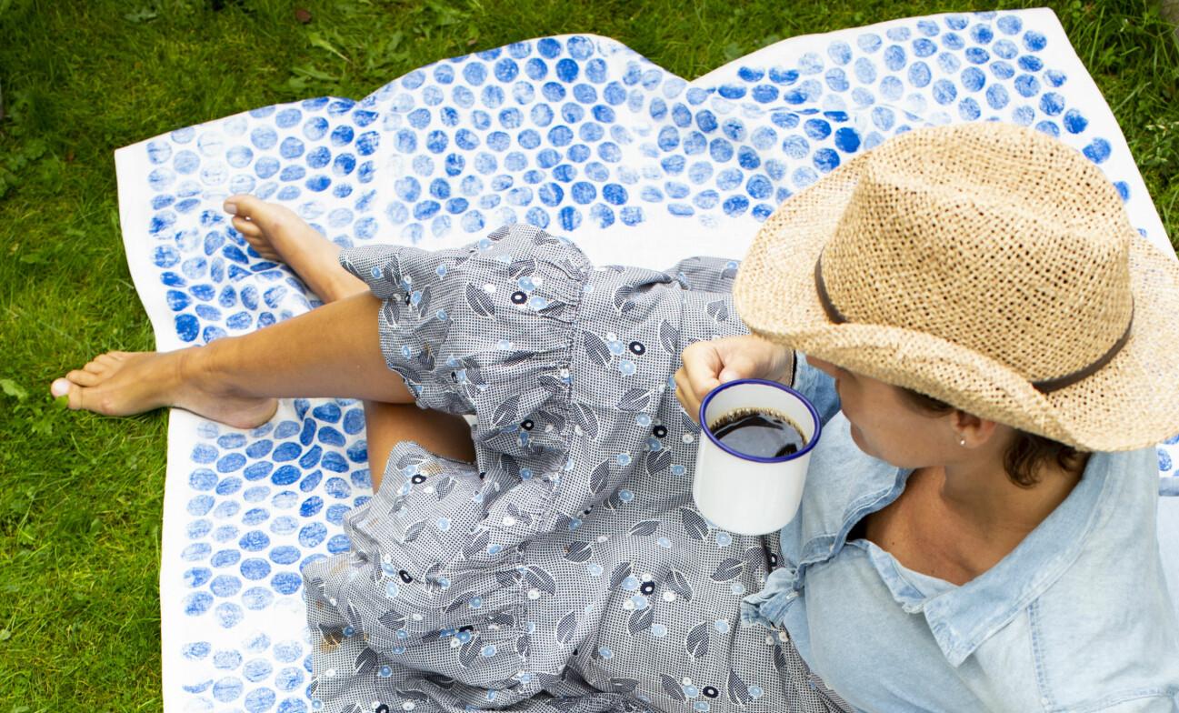 Kvinna sitter och dricker kaffe på en filt som fått mönster av bubbelplast.