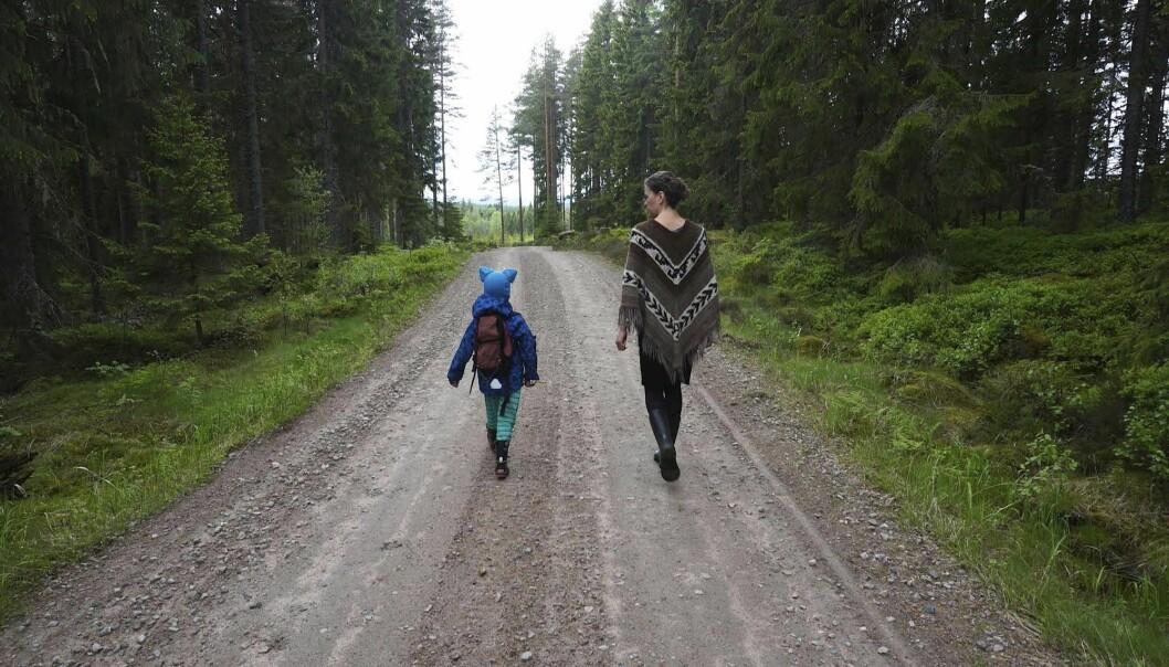 Mor och barn på promenad på en liten skogsväg.