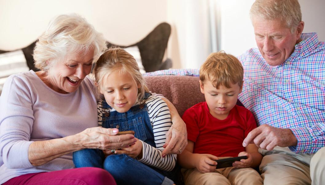 Mormor och morfar spelar spel med barnbarnen på telefonen.