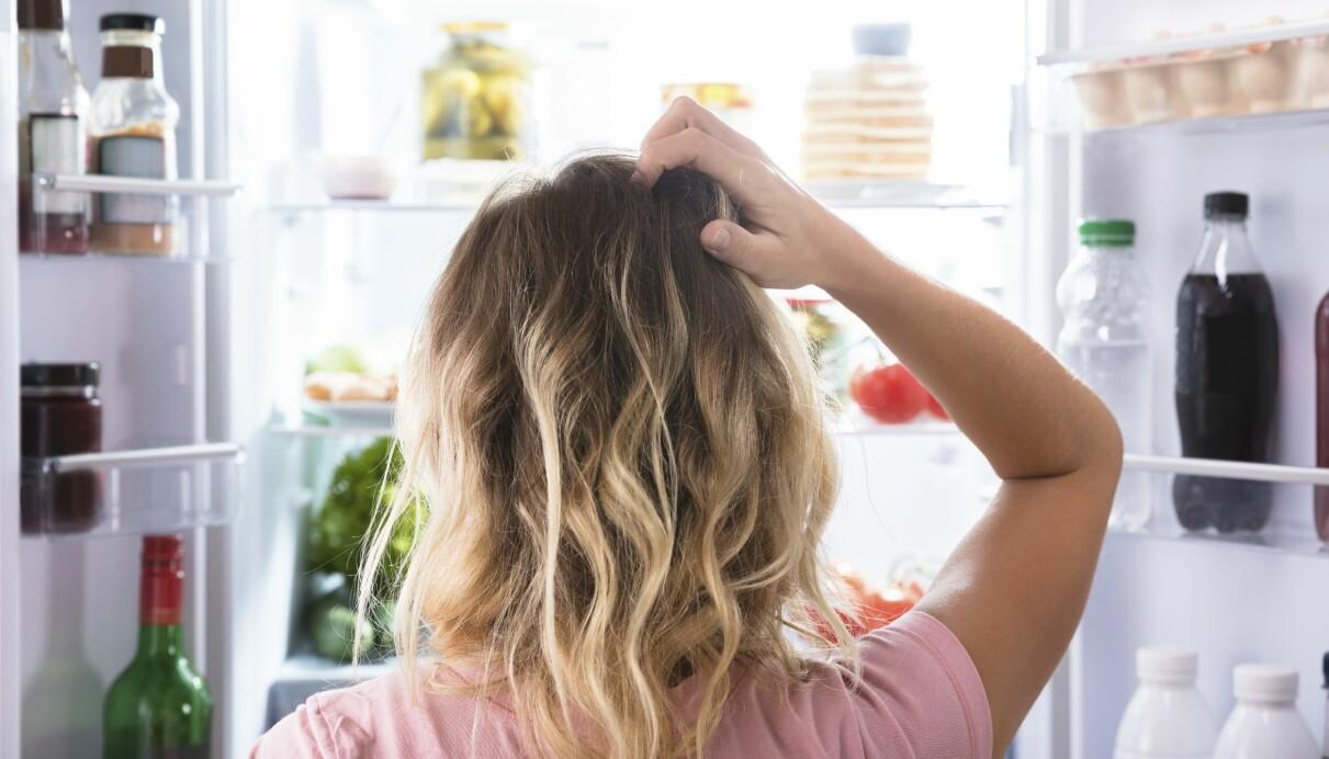 Kvinna tittar in i kylen, undrar om det finns någon nyttig mat