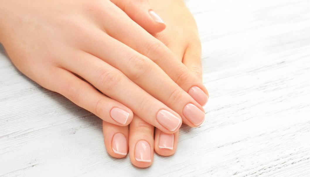 Händer på ett bord som visar upp sina fina naglar.