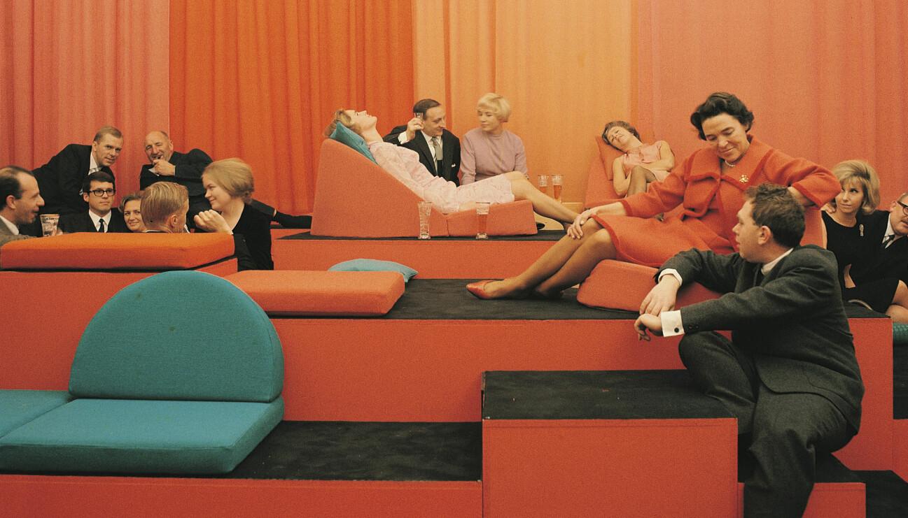 Kvinnor och män sitter i olika orange soffmoduler med orange draperi i bakgrunden.