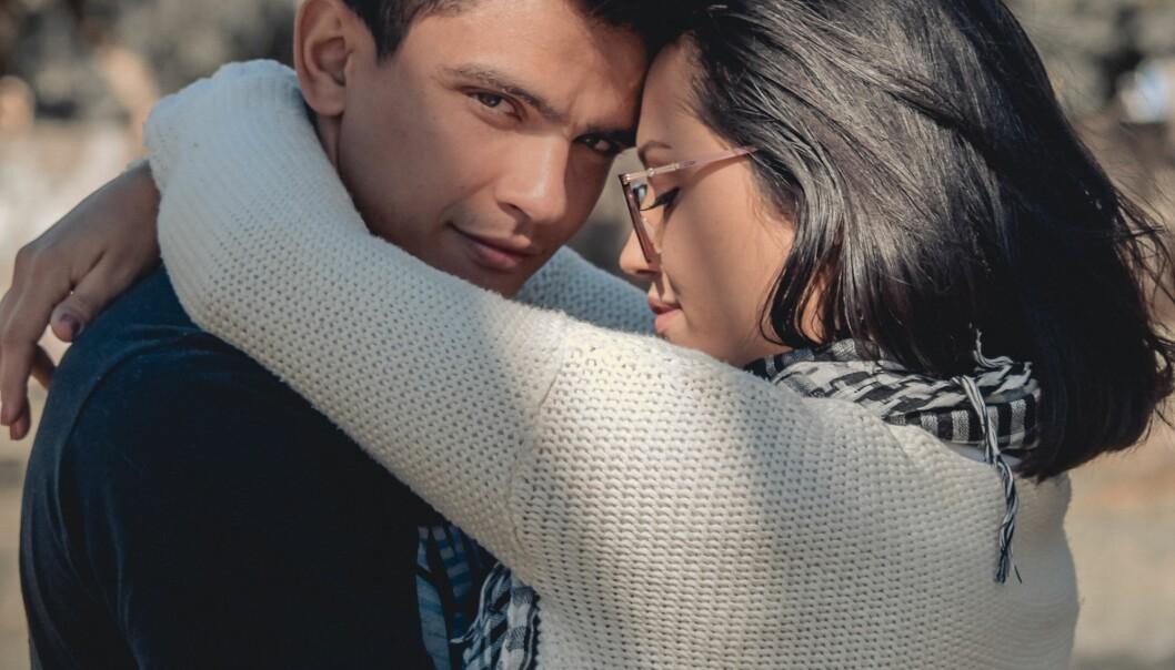 En narcissistisk man som står och kramar en kvinna som är intet ont anande.