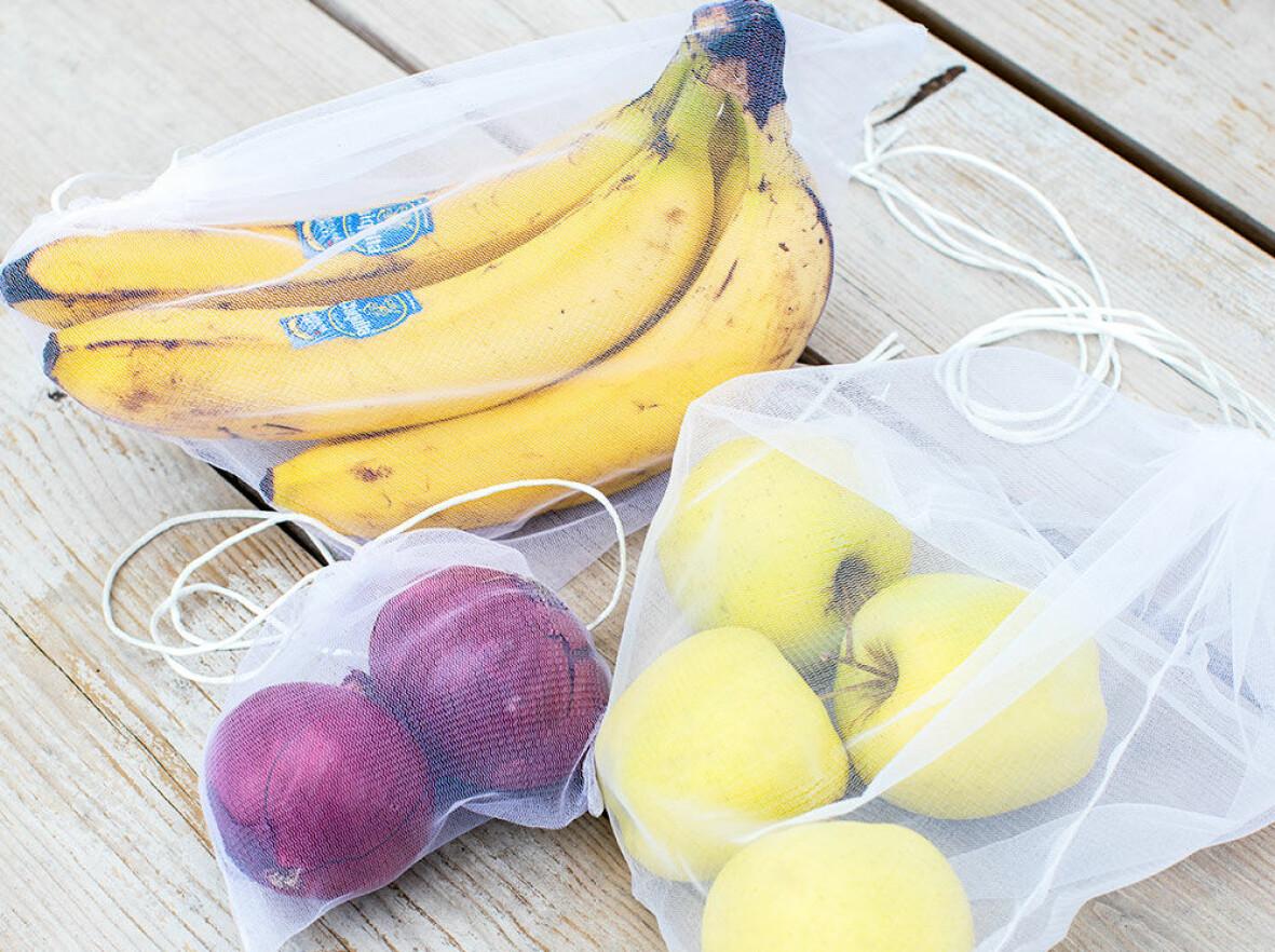Nätpåsar med frukt och grönsaker i.